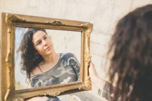 mujer mirando su rostro en un espejo