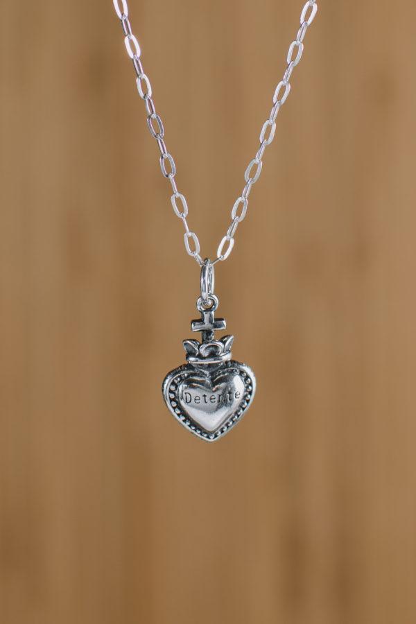 fondo de madera con colgante de corazon de plata colgando de una cadena delgada