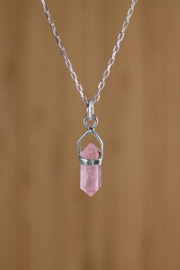 fondo plano de madera con imagen con zoom a colgante pequeño de piedra rosada con engaste de plata 925