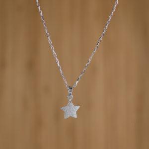 fondo de madera con colgante de plata con forma de estrella plana