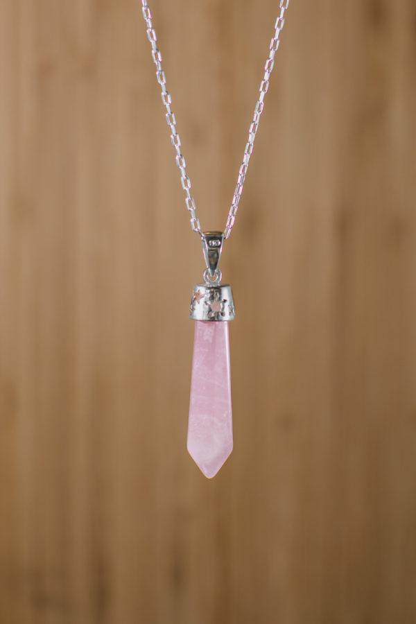 fondo de madera con imagen zoom a colgante de cuarzo rosado color rosado con engaste de plata y pequeños detalles de flores