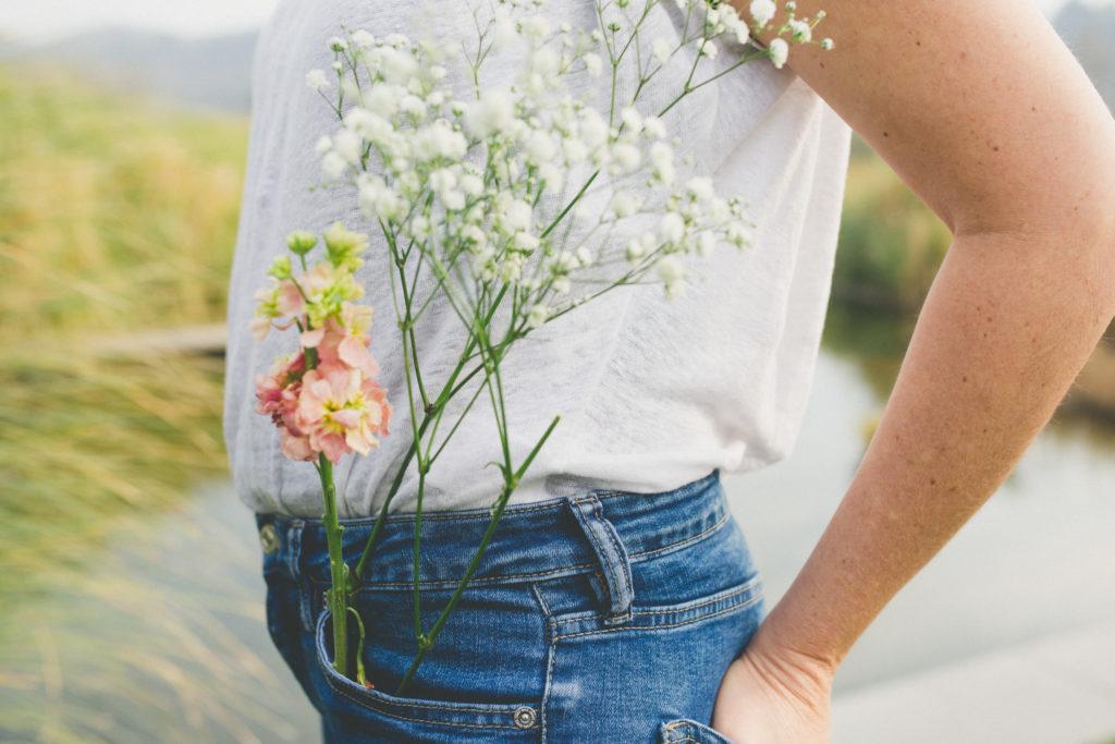 mujer de costado se ve solo su cintura con un ramo de flores en el bolsillo